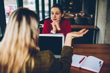 Pensive female graphic designer attentively listening colleague about productive strategy of developing startup business teamworking remotely at modern laptop computer connected to wireless internet
