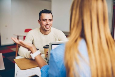 Cheerful male applicant for vacancy in company during conversation with female recruiter hiring for job,colleagues talking in friendly atmosphere joking during coffee break in modern office