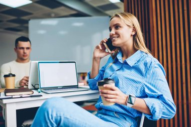 Cheerful blonde woman talking on mobile phone wit friend sitting at working place near laptop with mockup screen holding coffee cup,female employee having telephone conversation during work break