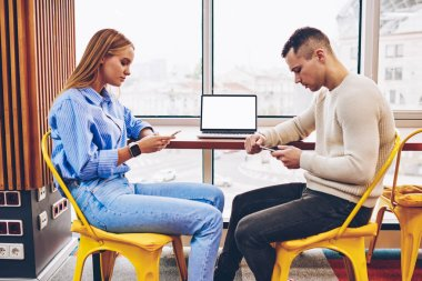 Students concentrated on social networks chatting ignoring communication with each other sitting in coworking space near laptop with mock up screen,colleagues addicted to modern technologies