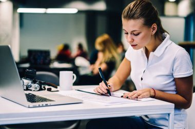 Concentrated clever female drawing schedule planning for organizing project task creation,skilled woman architect sitting at table with netbook in coworking space drafting graphic blueprint with ruler