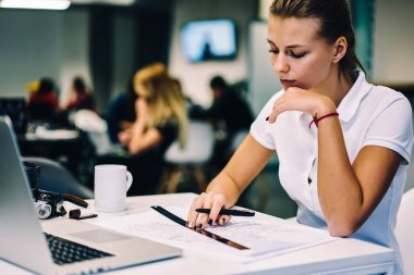 Thoughtful female designer pondering on project drawing sitting at working place with laptop computer, professionale woman employee creating schedule graphic for business plan analyzing accountings