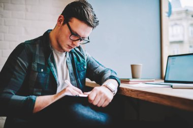 Concentrated smart male freelance writing article in notepad for editing before publication working remotely,clever hipster guy doing task for online course studying sitting in coworking space