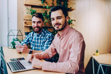 Portrait of skilled male it developers working on freelance spending time in coworking space, young hipster guys using modern technology and wireless connection for distance job sitting together