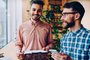 Portrait of handsome cheerful man holding folder with plans for successful startup cooperating with colleague, smiling hipster guy looking at camera during consultancy with friend about education