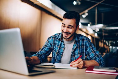 Cheerful hipster guy laughing at social networks content browsed on laptop computer during homework preparation in library, happy male student watching funny videos on netbook while learning