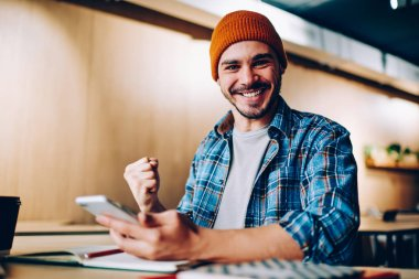 Portrait of cheerful hipster guy in hat making yes gesture overjoyed with victory in online contest holding telephone, amazed young man celebrating achievement in passing exams successfully get messag stock vector