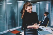 Fotografie Young charming contemplative female graphic designer dressed in formal wear writing down creative ideas to notepad while sitting on table.Intelligent woman employee making notes during work indoors