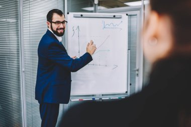Back view of female person listening to positive handsome male colleague explanation during standing next to board.Cropped image of skilled expert drawing flip chart graphics in modern office
