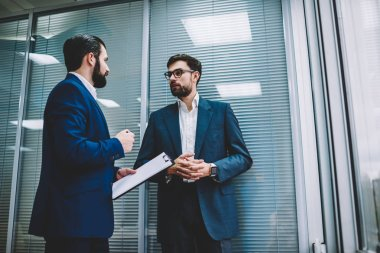 Intelligent bearded executive ceo holding folder with papers and explaining to colleague main ideas about working implementation.Skilled male experts sharing knowledge with each other in office
