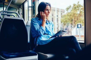 Thoughtful young woman looking out of window sitting in tram and listening audio songs on radio online in earphones connected to digital touch pad.Pondering hipster girl enjoying music from playlist