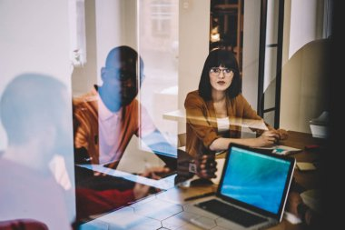 Diverse group of young people dressed in smart casual wear communicating with each other and discussing ideas for successful startup project sitting at meeting table in modern office behind glass wall