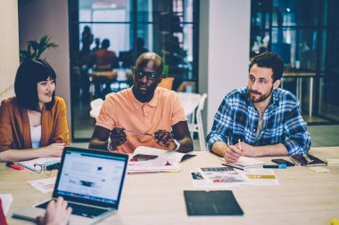 Group of diverse hipster student sitting at desktop with laptop computer having brainstorming meeting in coworking space.Smart casual dressed young people teamworking on common project in office