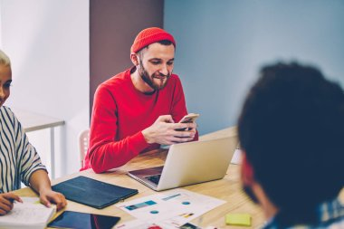 Cheerful young man chatting online on modern smartphone device while collaborating with colleagues during brainstorming at meeting table using 4G internet connection.positive male sending sms on phone