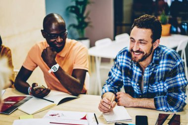 Cheerful caucasian young man laughing together with positive african american colleague collaborating on common task having brainstorming meeting in coworking.Smart casual dressed young people