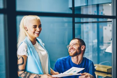 Cheerful young man and woman dressed in casual wear having fun while teamworking in modern office.Positive hipster guys laughing while discussing ideas for developing startup project