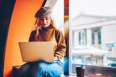 Cute young woman watching studying tutorial on laptop computer during free time in coffee shop,skilled  female freelancer creating content for website publication working remotely on netbook