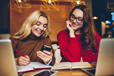 Cheerful female students having fun looking at photos on smartphone learning in coworking space together ,smiling hipster girl laughing on funny video browsed on cellphone working remotely cooperatin