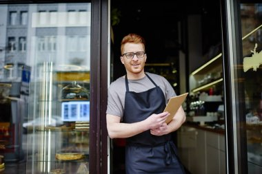 Portrait of cheerful owner of bakery holding menu and inviting to shop.Positive waiter in apron smiling at camera while standing outdoors at entrance to cafe and showing hospitality