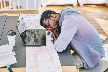 Dark skinned male architect sleeping at desktop working overtime and feeling tired, exhausted african american freelancer workaholic completing project before deadline stressed and frustrate