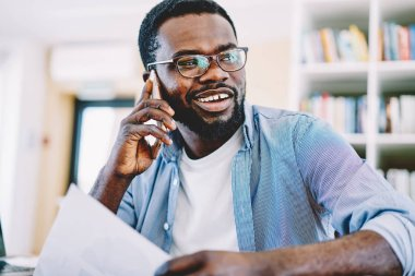 Cheerful dark skinned hipster guy in eyewear looking away having telephone conversation smiling, young african american man satisfied with consultance with service operator during cellphone talk