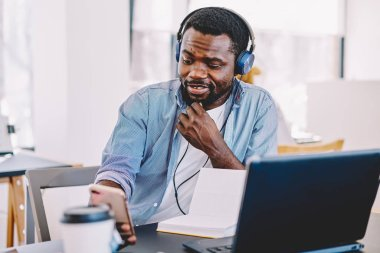 Pensive dark skinned male in headphones listening music in headphones from playlist on smartphone, african american guy using 4G internet for making video call via cellular sitting in coworking space