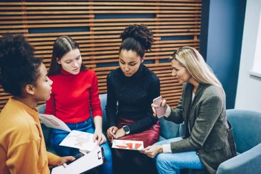 Professional female designers discussing organization of new fashion collection checking sketches, multiracial women friends choosing clothes looking at drawings of dressmaker during consultancy