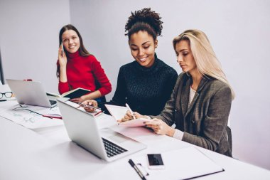 Serious multiracial women preparing report for startup searching information from different sources, working crew of female designers concentrated on their tasks using modern technology in office