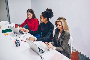 Young female students having conversation about homework consultation sitting at desktop, multiracial crew of women colleagues using modern technology for working process cooperating in office