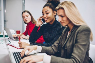 Crew of multiracial female colleagues busy with organization startup using modern technology for working process, professional women partners cooperating in team completing project preparations