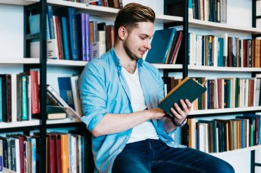 Concentrated smart hipster student reading textbook and preparing for studying seminar.Pensive young man holding literature book in hands sitting on chair near bookshelf in public library