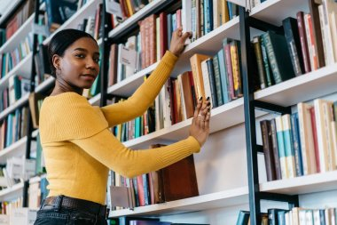 Half length portrait of african american young woman in casual wear looking at camera while pulling literature book from bookshelf in public library.Dark skinned student choosing textbook for studying
