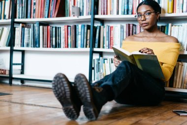 Portrait of attractive african american young woman looking at camera while sitting on floor near bookshelf and reading book.Charming smart dark skinned student with literature bestseller in library