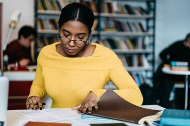 Pensive smart african american student reading studying task and doing homework in library.Concentrated dark skinned young woman in eyeglasses preparing for seminar sitting at desktop with copybooks