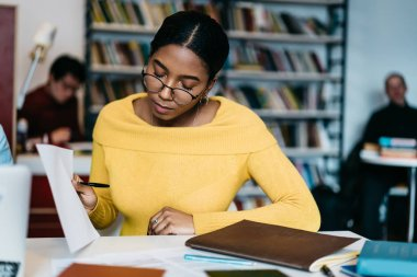 Concentrated african american hipster student in eyeglasses reading studying test and preparing for upcoming exams sitting at desktop in library.Pensive dark skinned young woman checking compendium