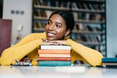 Positive african american young woman dressed in casual wear laughing and looking away.Cheerful dark skinned student smiling while sitting at desktop with many studying books for exam preparation