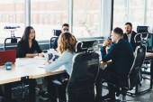 Obchodní setkání mladých mužských a ženských podnikatelů na sobě formální oblečení v moderních kancelářských interiérů. Zaměstnanci na setkání tabulky během konference se pyšní ceo v finanční společnosti