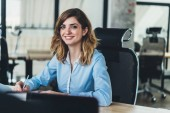 Fotografie Portrait of prosperous beautiful young woman dressed in formal wear smiling at camera while writing down plan organization of working process.Cheerful businesswoman making notes sitting at table