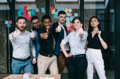 Fotografie Portrait of multicultural team of happy office employees dressed in formal wear holding thumb up showing sign okay and success of collaboration standing against wall with colorful stickers in office
