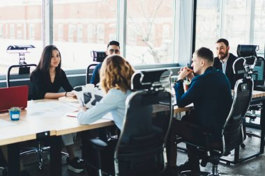 Business meeting of young male and female entrepreneurs dressed in formal wear in modern office interior.Employees sitting at meeting table during conference with proud ceo in finance company