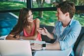 Pozitivní mladý muž a žena smíchy při vzájemné komunikaci a tráví volný čas spolu na notebooku v kavárně. Veselí studenti diskuse o procesu spolupráce na projektu