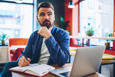 Pondering bearded creative man in denim apparel thinking on productive ideas for developing own startup project sitting at modern laptop computer and notepad for notes in stylish coworking space