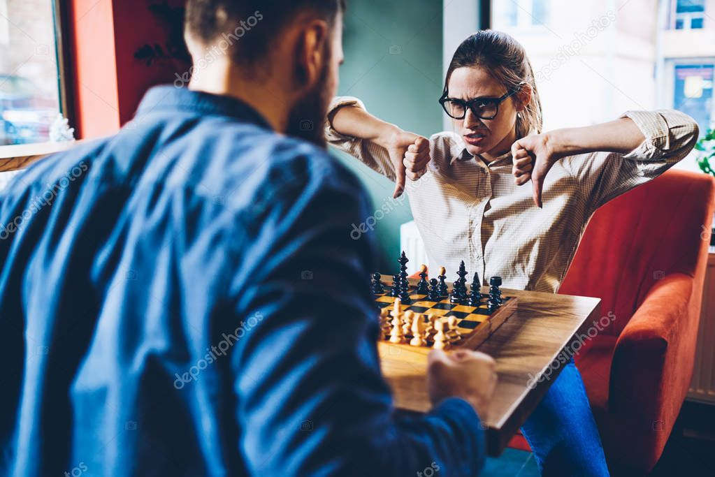 Serious professional female player accepted challenge from male rival and gesturing thumb down showing fail in intelligent game in chess.Angry woman with loser sign deriding opponent during battle