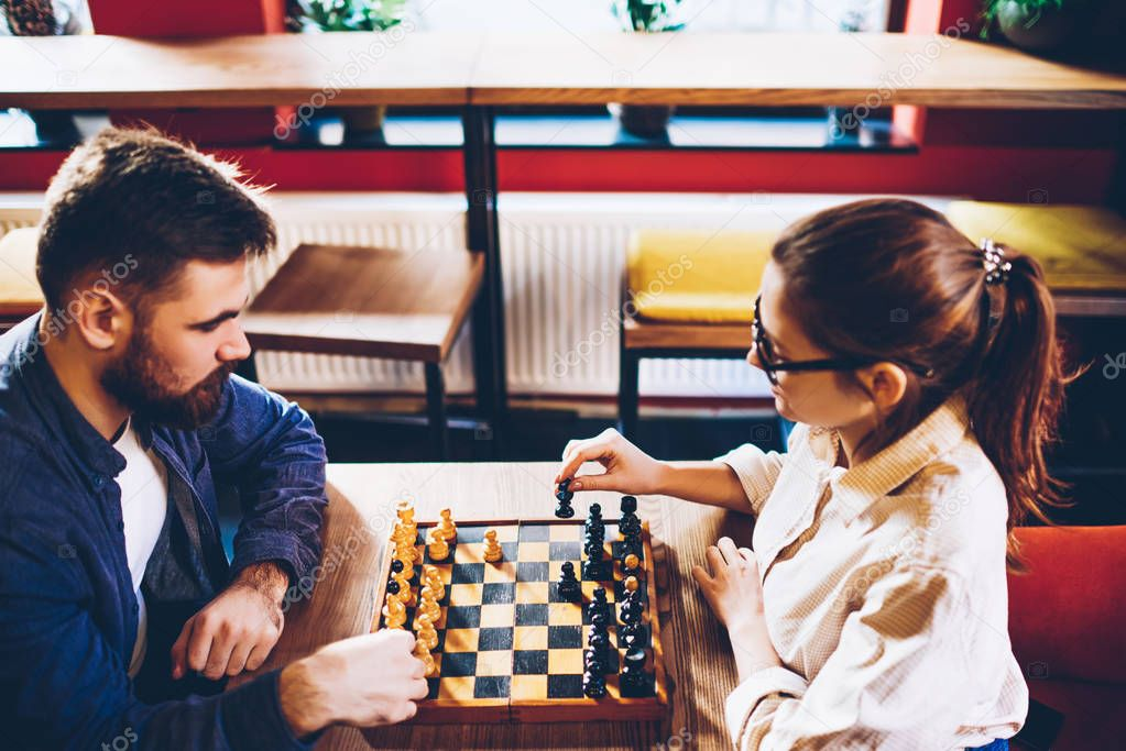 Top view of two intelligent hipster students playing in chess in leisure time.Concentrated young woman holding black pawn and making move on chessboard to do checkmate to colleague during sport battle