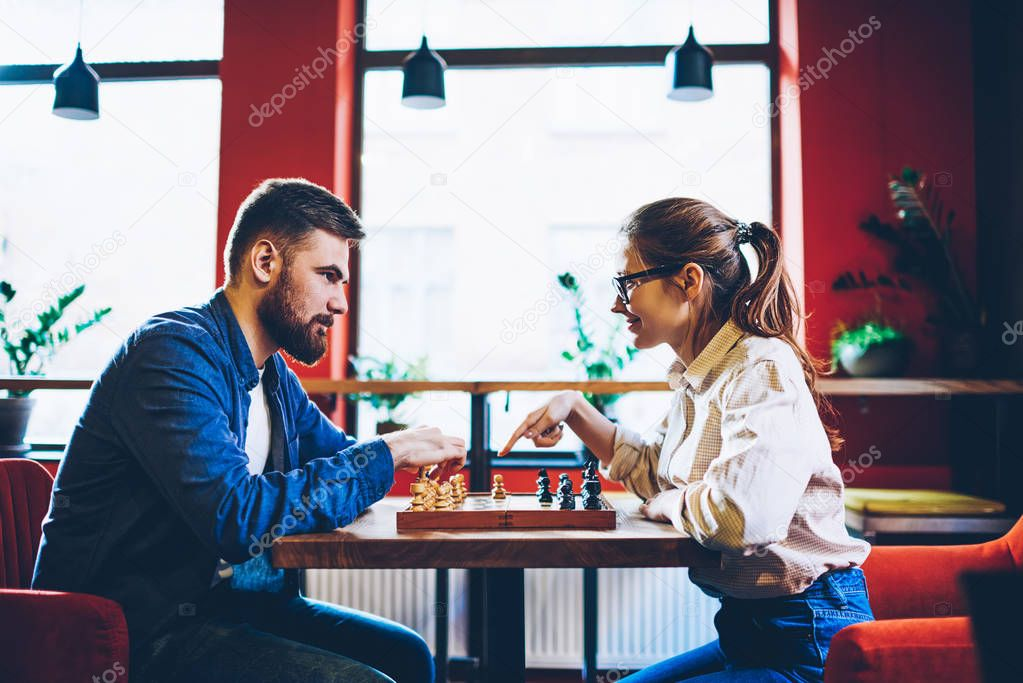 Side view of couple in love playing in chess enjoying hobby together.Cheerful young woman pointing on pawn to asking in boyfriend about sport tactic on chessboard during intelligent game