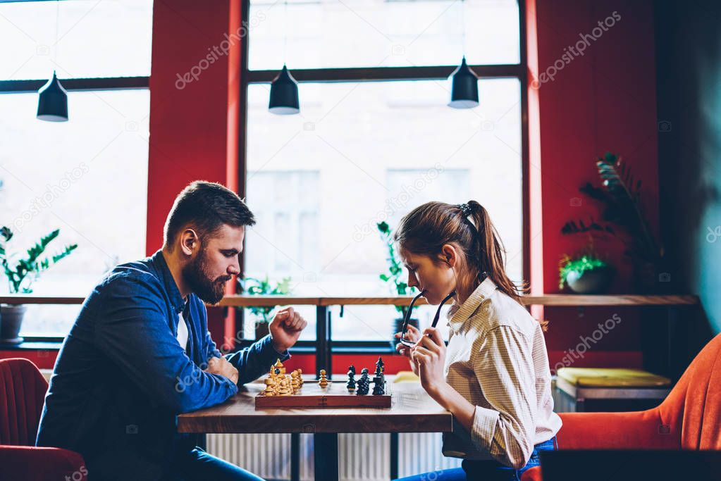 Side view of concentrated two hipsters thinking on tactical strategy of next move on chessboard during sport competitions in chess.Young couple in love playing in favourite game in free time