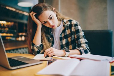 Tired female student preparing for important exam trying find answers for questions using modern laptop and books indoors, concentrated woman feeling headache from course work at university library