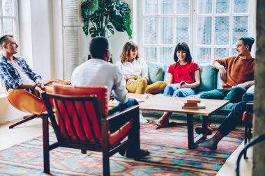 Positive diverse young people dressed in casual wear spending free time together enjoying communication with each other in stylish apartment.Cheerful multicultural hipsters laughing during game