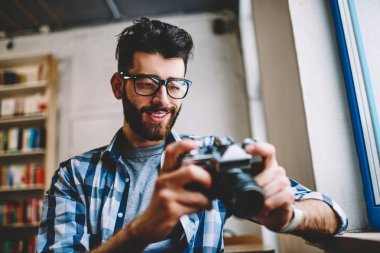 Successful hipster guy waiting friend in bookstore while checking photos at vintage camera during free time, happy stylish smiling man wear in trendy apparel holding old fashioned equipment