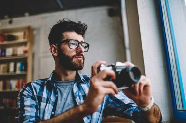 Thoughtful hipster guy wear in spectacles for vision correction looking in window after making images via retro camera, concentrated professional male photographer enjoying time and hobby indoors